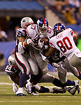 New York Giants running back Brandon Jacobs (27) is gang tackled by the New England Patriots defense during the NFL Super Bowl XLVI football game on Sunday, Feb. 5, 2012, in Indianapolis. The Giants won 21-17 (AP Photo/David Stluka)...
