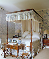 Matching blue-and-white toile de Jouy wallpaper and bed hangings combined with an antique four-poster bed result in a bedroom of 18th century-style elegance