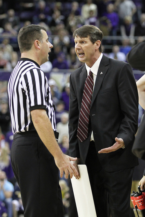 Ken Bone, Washington State head basketball coach, discusses the finer points of officiating with one of the officials during the Cougars 80-69 road victory over arch-rival Washington at the Alaska Airlines Arena in Seattle, Washington, on February 27, 2011.  With the victory, Coach Bone and the Cougars swept the regular season series from the Huskies, two games to none.
