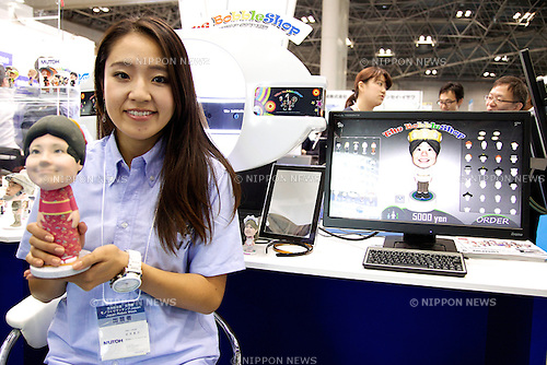 """An exhibitor shows a figure made by The Bobble Shop which can create 3D figures from scanner face at Robot Week 2014 on October 16, 2014 in Tokyo, Japan. Companies at the """"Japan Robot Week 2014"""" exhibited their latest high-tech nursing and life supporting robots. The 2014 edition of the show ran from October 15 to 19 at Tokyo Big Sight. (Photo by Rodrigo Reyes Marin/AFLO)"""