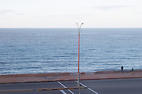 Coast line at dawn. Empty street. Lamp post with two persons and a dog. Montevideo, Uruguay, South America