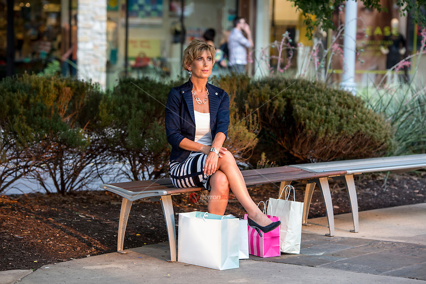 Attractive female shopper rest on a bench from a busy day shopping at an Austin outdoor shopping mall