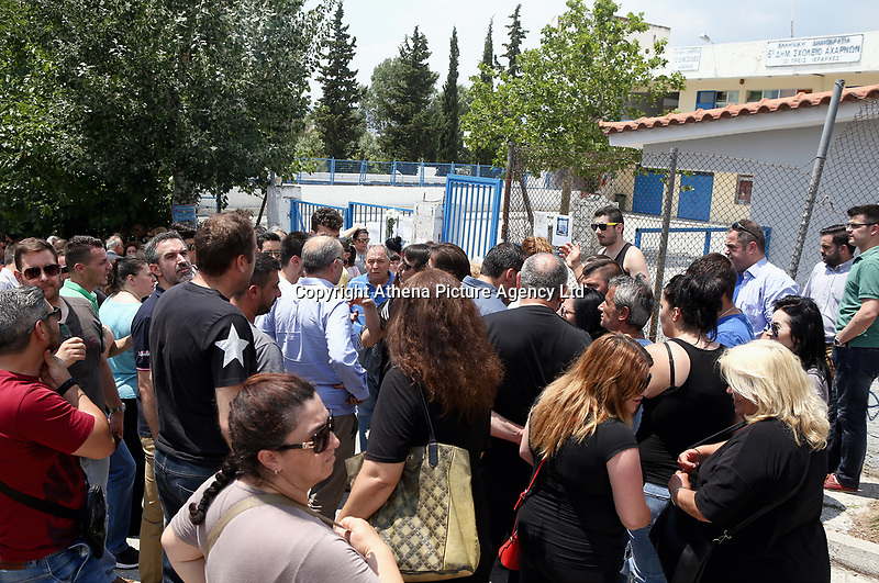 """Pictured: Local people show their solidarity by gathering outside the 6th primary School in Acharnes, Athens, Greece. Saturday 10 June 2017<br /> Re: An 11 year old boy has been shot dead by a """"stray bullet"""" during a school celebration in Acharnes (Menidi) area, in the outskirts of Athens, Greece.<br /> Marios Dimitrios Souloukos """"complained to his mum"""" who works as a teacher at the 6th Primary School of Acharnes that he was feeling unwell, he then collapsed with blood pouring out from the top of his head.<br /> His mum tried to revive him assisted by other teachers while his schoolmates who were reportedly upset, were hurriedly removed by their parents.<br /> According to locals an ambulance arrived 25 minutes late.<br /> Hundreds of police officers have been deployed in the area and have raided many properties.<br /> Shells matching the fatal bullet which hit the boy on the top of his head were found in a house yard nearby.<br /> Local people reported hearing shots being fired at a nearby Romany Gypsy camp before the fatal incident.<br /> The area has been plagued with criminality during the last few years."""