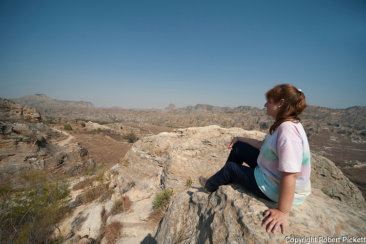 Young woman sitting looking at landscape view of Sandstone rock formations, Isalo National Park, Madagascar, deep canyons, palm lined oases, and grassland