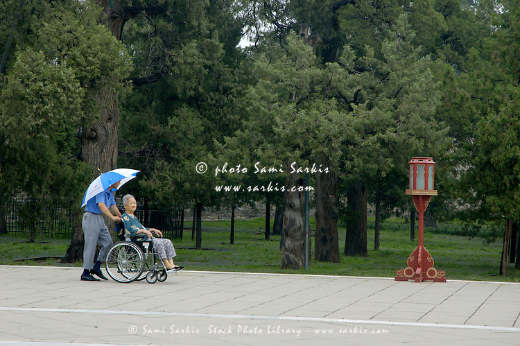 Man pushing a disabled woman on a wheel chair through Tiantan Park after visiting the Temple of Heaven, Beijing, China.