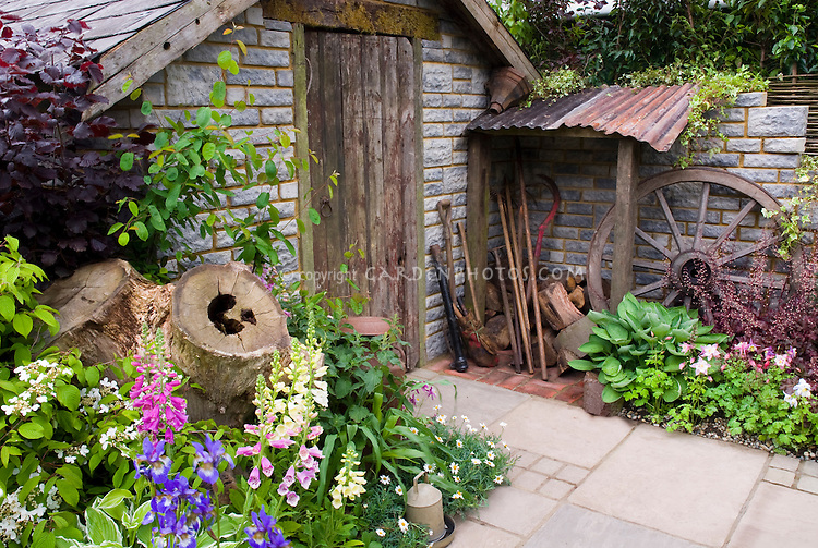 Old stone garden shed with beautiful flower garden for Flower garden ornaments