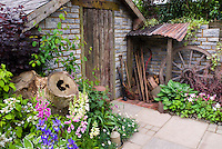 Rustic old farm tools, country style garden, ornaments, old brick shed, patio, wall, charming old fashioned feel to the garden mixed with vegetables, flowers, iris, Digitalis, Viburnum shrubs, Heuchera in flower, lettuce, herbs, vines, wagon wheel
