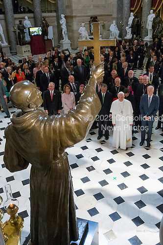 Pope Francis (2-R) pauses in front of a sculpture of Spanish-born Junipero Serra, the Franciscan Friar known for starting missions in California, in Statuary Hall at the U.S. Capitol in Washington DC, USA, 24 September 2015. Pope Francis is on a five-day trip to the USA, which includes stops in Washington DC, New York and Philadelphia, after a three-day stay in Cuba. Pope Francis added the Cuba visit after helping broker a historic rapprochement between Washington and Havana that ended a diplomatic freeze of more than 50 years.<br /> Credit: Michael Reynolds / Pool via CNP