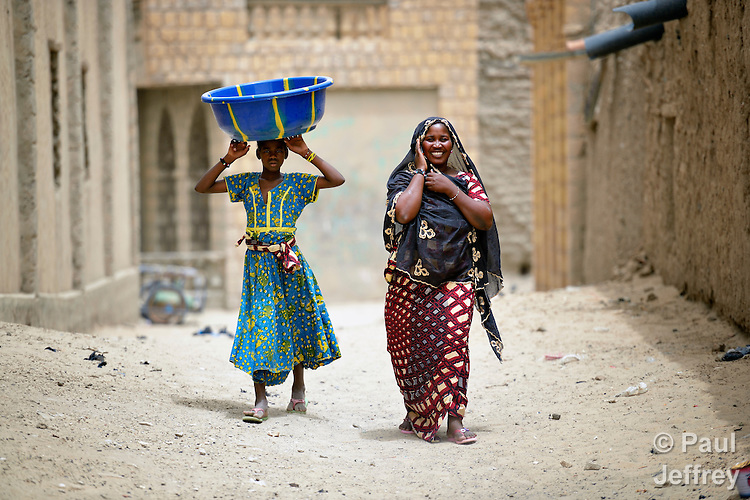 Two women from two classes walk along a street in Timbuktu, a city in northern Mali which was seized by Islamist fighters in 2012 and then liberated by French and Malian soldiers in early 2013. The woman on the left is a member of the Bella ethnic group, who often work as servants, even slaves, to other dominant ethnic groups.