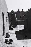 A young man runs along a laneway behind the Grand Mosque. Most of the buildings in the town are made from mud brick, or adobe, popular due to its ability to insulate from the heat. The outer mud layer is reapplied each year after the seasonal rains.