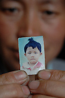 Guo Xiu Li, who was eight and half years old when she was stolen from her parents house. She was stolen in September 2004 and despite their best efforts their parents have been unable to find her. Her mother, Li Ren Xiu, 39, holds the photograph, June 2007. The trade in girls and women is increasing as the sex imbalance has reached a national average of 120 males for every 100 females, in some areas the ratio is as high as 168 males for every 100 females..PHOTO BY SINOPIX