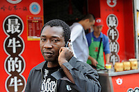 CHINA Guangzhou , african trader buy  textiles in export- and wholesale markets which the ship to Africa for their shops, Nigerian Ikechukwu Nwanzi making deals by phone / CHINA , Provinz Guangdong , Metropole Guangzhou (Kanton) , Haendler aus Afrika kaufen in Grosshandels-/Exportmaerkten Textilien fuer Ihre Laeden in Afrika ein, Nigerianer Ikechukwu Nwanzi mit Mobiltelefon