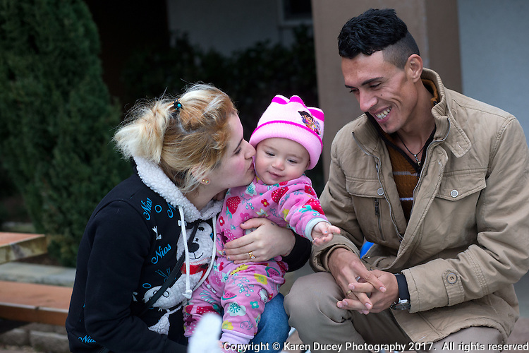 Shatha Sulaiman Kheder, (left), her son Steven Adil Kheder, 10 months, and husband Adil Kheder Nimr, (right) share a moment outside their new apartment in Tukwila, Washington on January 30, 2017.  The family arrived in the United States on as refugees from Iraq on January 19, 2017, the day after Donald Trump was sworn in as the 45th president of the United States. They are concerned about thirteen of their family members still in Iraq. Trump signed an executive order last Friday restricting immigration from seven Muslim countries, suspending all refugee admission for 120 days, and bans all Syrian refugees indefinitely.  (Photo by Karen Ducey)