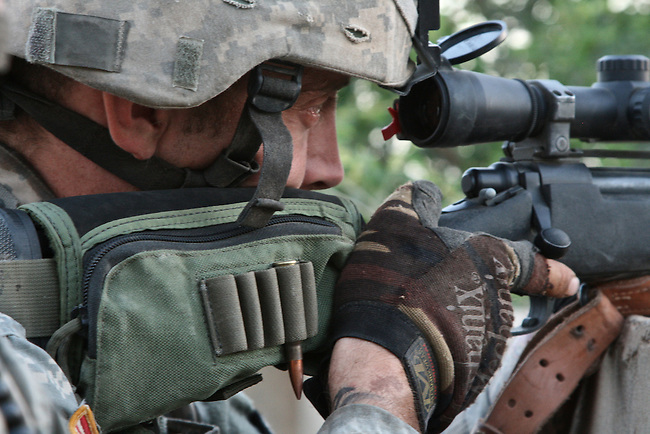Spc. Josiah W. Hollopeter, 27, of Valentine, Neb. peers through his rifle scope, hoping to spot an insurgent sniper near Patrol Base K-Wal, in the village of Shakarat, in Diyala province, Iraq. A soldier with Troop C, 6th Squadron, 9th Cavalry Regiment, Hollopeter has been on the hunt for two months, after the enemy marksman killed another U.S. soldier in March. Hollopeter died eight days after this photo was taken, when his four-man sniper team was ambushed by insurgents. June 6, 2007. DREW BROWN/STARS AND STRIPES