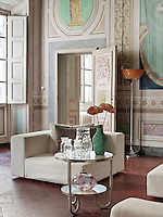In a spacious drawing room in the Palazzo Orlandi, simple modern white seating and a contemporary side table contrast with, yet compliment, the traditional richly decorated walls by Luigi Catani, a leading 18th century fresco painter.