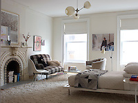 Another bedroom features a vintage sofa paired with an Eames chair and a pendant light by Lindsey Adelman