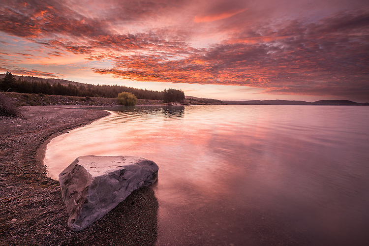 NZ landscape image of a vivid sunrise over Lake Pukaki, Mackenzie Country. Wedge shaped rock in foreground.