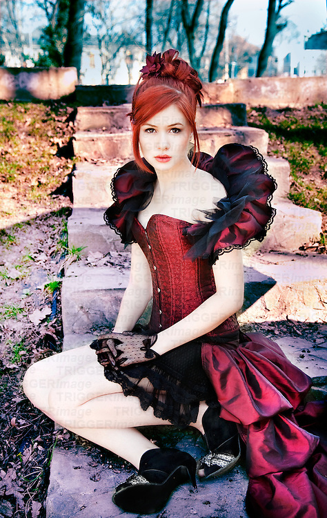 girl in red victorian corset with ruffle, sitting on steps outdoors