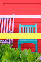 A pair of painted chairs has been placed against the striking red clapboard exterior of this beach hut