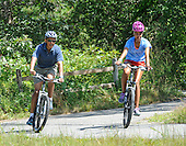 United States President Barack Obama goes bike riding with his daughter Malia during their vacation in West Tisbury on Martha's Vineyard, Massachusetts on August 16, 2013. They were joined on the ride by First Lady Michelle Obama (not pictured) and daughter Sasha Obama (not pictured).<br /> Credit: Rick Friedman / Pool via CNP