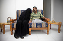 Moemen Faiz, a photographer, sits with his new wife, Deema Ayideh, at the couple's home in Gaza. Faiz was injured during Israel's assault on Gaza in the winter of 2008-09, and was later flown to Saudi Arabia where he received treatment. The two fell in love when Ayideh, a journalist, interviewed Faiz at the hospital, and they married soon after [Tanya Habjouqa]