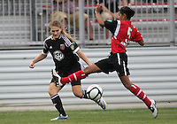 BOYDS, MARYLAND - July 21, 2012:  Ashley Herndon (19) of DC United Women slips the ball past Taylor Mertz (5) of the Virginia Beach Piranhas during a W League Eastern Conference Championship semi final match at Maryland Soccerplex, in Boyds, Maryland on July 21. DC United Women won 3-0.