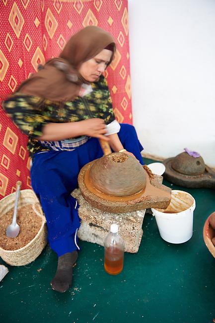 Women milling roasted Argan nuts at the Cooperative Marjana, Ounara, Essouira, Morocco