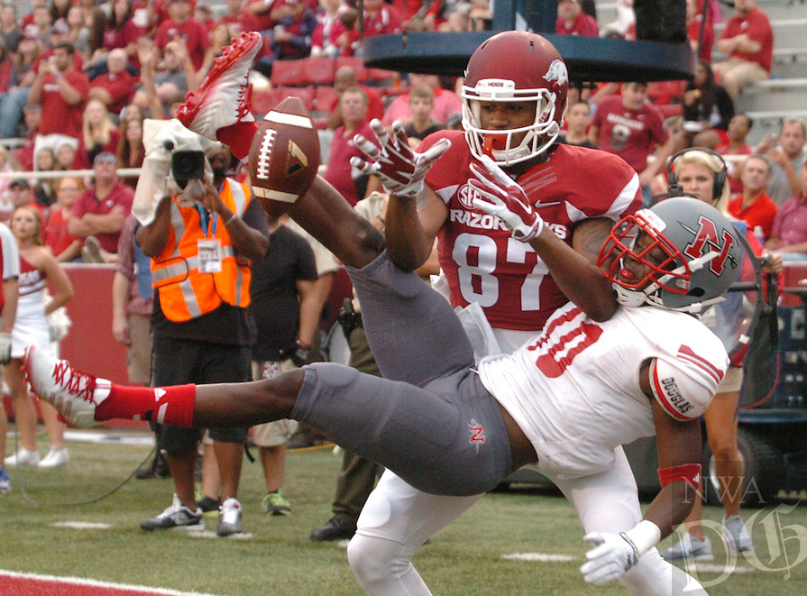 NWA Media/ANDY SHUPE - Arkansas receiver Kendruck Edwards (87) reaches for the ball as Nicholls defensive back Josh Dewey is upended during the second quarter Saturday, Sept. 6, 2014, at Razorback Stadium in Fayetteville