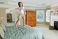 A six year old girl jumping on her parent's bed.