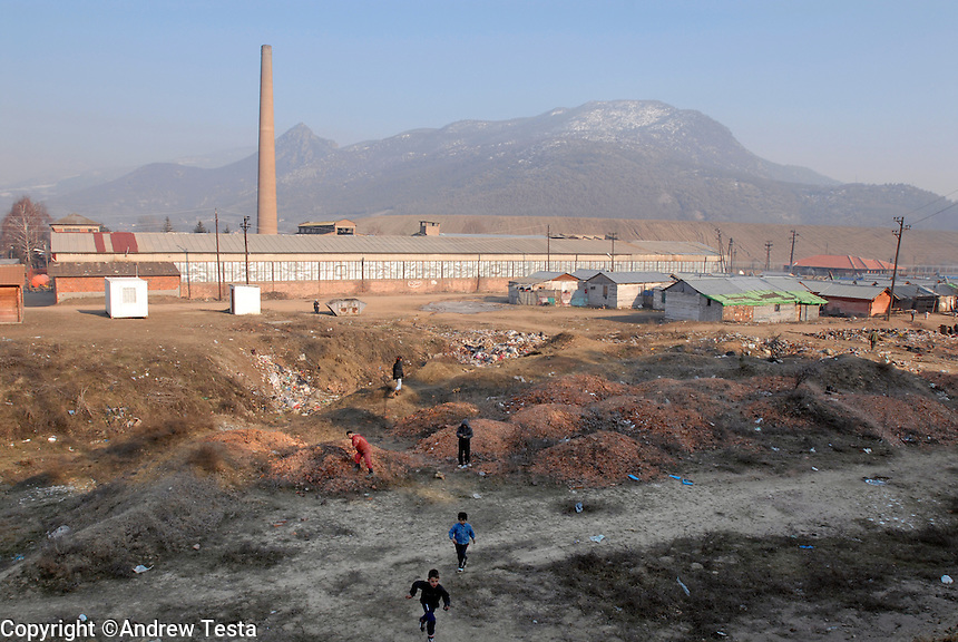 KOSOVO. Zvecan.28th January 2006..Roma children play on lead contaminated land near their camp in Zvecan. A slag heap of toxic waste lies behind their homes..©Andrew Testa for the New York Times