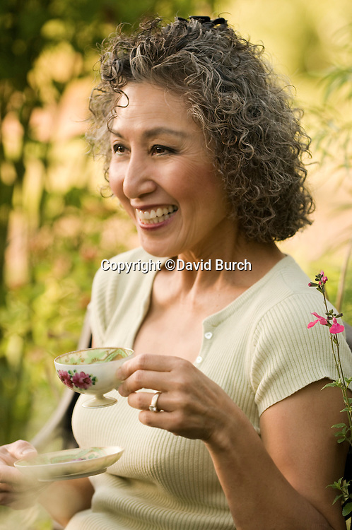 Asian woman drinking tea and smiling in her garden