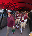 The shadows of Seminole fans silhouette the canopy as Florida State head coach Jimbo Fisher leads his team through the tunnel to play the Florida Gators.   The Florida State Seminoles defeated the Florida Gators 24-19 in an NCAA football game in Tallahassee, November 29, 2014.