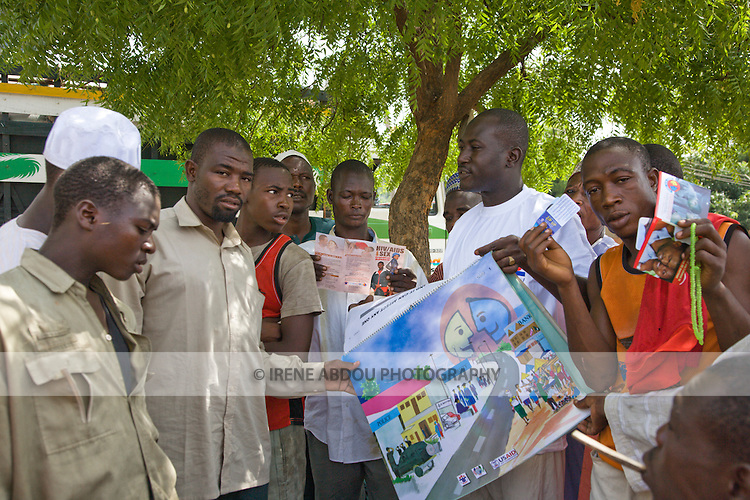 An HIV/AIDS prevention volunteer talks to men in Yankaba market in Kano, Nigeria, about how partner reduction reduces chances of HIV/AIDS transmission.  He uses a pictoral flipchart designed for low-literacy audiences by the Society for Family Health (SFH), Nigeria's largest indigenous non-profit and affiliate of the international social marketing organization, Population Services International (PSI).                                               (Nassarawa area, Kano, Nigeria)