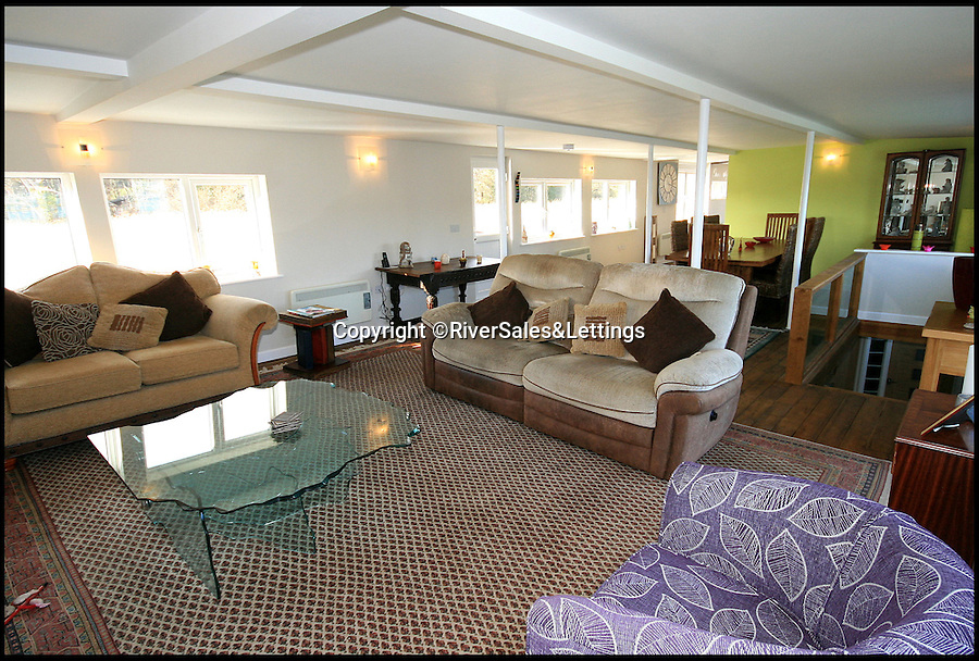 BNPS.co.uk (01202 558833)<br /> Pic: RiverSales&amp;Lettings/BNPS<br /> <br /> ****Please use full byline****<br /> <br /> Lounge.<br /> <br /> A 100-year-old barge once used to ship cargo up and down the River Thames has been transformed into a plush four-bedroom house that is now on the market for &pound;450,000.<br /> <br /> The 90ft boat was salvaged from the banks of Thames in the 1970s and turned into a floating dormitory for schoolchildren at an outdoor activity centre.<br /> <br /> But it has since been given a complete makeover and now looks more like a cosy country cottage than a boat.<br /> <br /> The two-storey houseboat runs off mains electricity, has wifi access, electric heating, and hot water, and it also has a reserve water tank stored in its funnel.<br /> <br /> And buyers can count the picturesque River Hamble near Southampton, Hants, as their back garden.