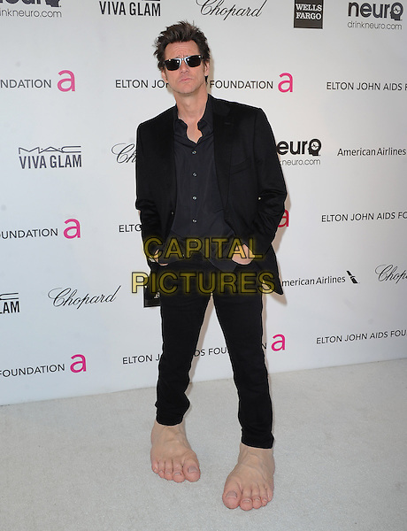 Jim Carrey.The 21st Annual Elton John AIDS Foundation Academy Awards Viewing Party held at The City of West Hollywood Park in West Hollywood, California, USA..February 24th, 2013.oscars full length black suit sunglasses shades hands in pockets funny giant large side oversized feet make-up prosthetics .CAP/DVS.©DVS/Capital Pictures.