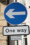 Circular blue sign with arrow, one way street, England