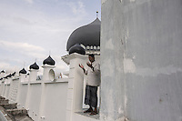 "Indonesia – Sumatra – Aceh – Lampuuk – Sulaiman Amin, the 62-year-old imam prays on the rooftop of the mosque, the only building still standing in the whole village after the tsunami. Amin was caught by the waves in his house, together with his 18-year-old son and his wife. He remembers that the waters had reached the height of the dome. It was the only visible thing in a village that had turned into open sea. Amin ended up five km inland and was rescued in the evening. He had lost his wife, his son and his livelihood, a small rice processing factory for which he never received any compensation. ""Now I have no pension, no income and I have to survive on the alms of the people"". Three years after the tsunami, Amin was chosen as the new imam from the community, a job he takes very seriously. ""I survived because of God's will"" he says convincingly."