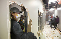 Daniel Godfrey of Fayetteville breaks through a wall Saturday, Jan. 11, 2020, while doing interior demolition with other church members at 101 W. Mountain Street on the Fayetteville square. <br /> <br /> Christ Community Church purchased the building and will work with Milestone Construction Company to renovate the space into their permanent home. Art Ventures NWA moved out of the building in December and the Fayetteville Farmers Market will keep their office in the building. <br /> <br /> The church formed six years ago, said Andrew Brill, director of operations, and currently rents space at Mount Sequoyah Retreat and Conference Center. They hope to move into the new space in August. <br /> <br /> The church uses multiple spaces spread across the Mount Sequoyah campus, said Brill, and they wanted a location with everything under one roof. Brill and lead pastor Hunter Bailey both said that the church wanted to be closer to the heart of Fayetteville. Bailey said that he wants people to know the building is 'Still a community place - a place that serves Fayetteville.' <br /> <br /> Check out nwaonline.com/200112Daily/ for today's photo gallery.<br /> (NWA Democrat-Gazette/Ben Goff)