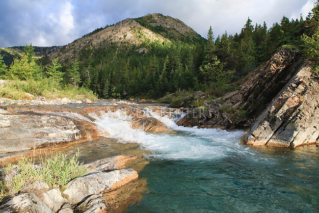 The waters of Strawberry Creek flow over a small falls into a deep clear pool on its way out of the Bob Marshall Wilderness in Montana