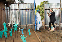 Occidental College professor Mary Beth Heffernan photographs health care worker Martha Lyne Freeman at ELWA II Ebola Treatment Unit (ETU) in Monrovia, Liberia on Thurs., Feb. 24, 2015. The photos will be used in Professor Heffernan's PPE Portrait Project.<br /> (Photo by Marc Campos, Occidental College Photographer) Mary Beth Heffernan, professor of art and art history at Occidental College, works in Monrovia the capital of Liberia, Africa in 2015. Professor Heffernan was there to work on her PPE (personal protective equipment) Portrait Project, which helps health care workers and patients fighting the Ebola virus disease in West Africa.<br />