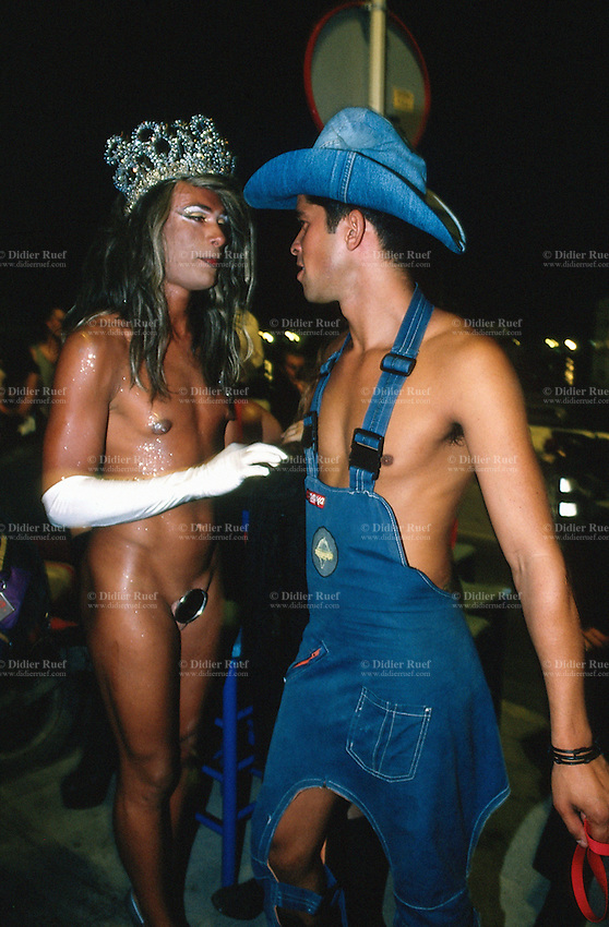 Spain. Ibiza in the Balearic islands. Ibiza. Night life. Two sexy young men, both gays, talk at the terrace of a café.  One is fully naked with just a mirror to hide his penis. He wears a queen's crown on his head. The other is dressed in jeans as a cowboy with a hat on his head. Transsexualism is a condition in which an individual identifies with a physical sex that is different from their biological one. © 1999 Didier Ruef
