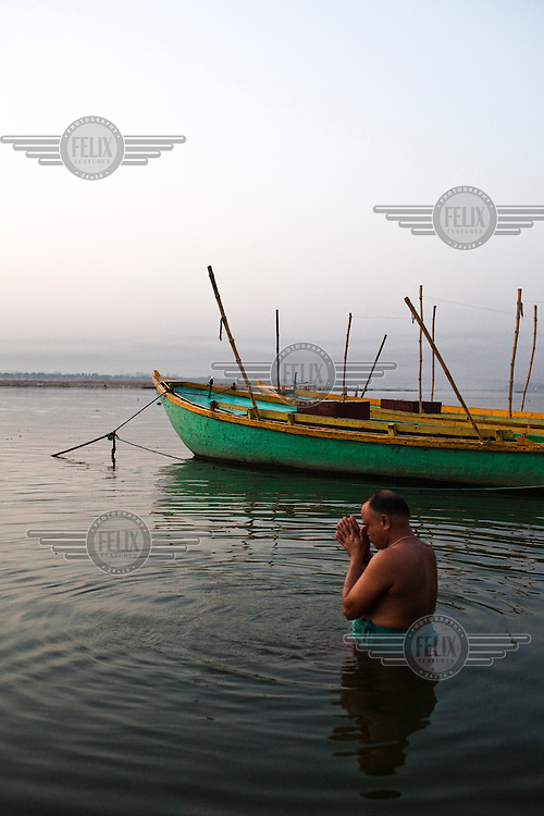 A religious Hindu priest offer prayers and takes a bath at dawn on the ghats of the Ganges River in the ancient city of Varanasi.
