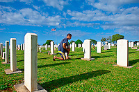 Hawaiian man paying respects at graveside to fallen friend at Makawao Veterans Cemetery, Makawao, Maui