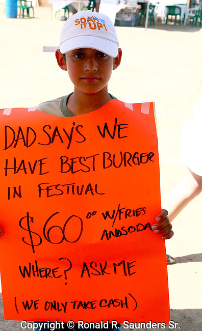 Young boy carries a poster  marketing his father's fast food business during the Annual Blues & Arts Festival