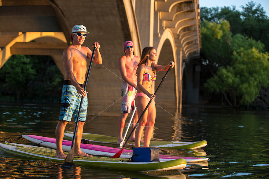 Three happy fit and attractive young adults on paddle boards navigate Lady Bird Lake, Colorado River, Austin, Texas.