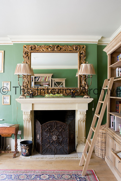 Stone fireplace with mirror in library room