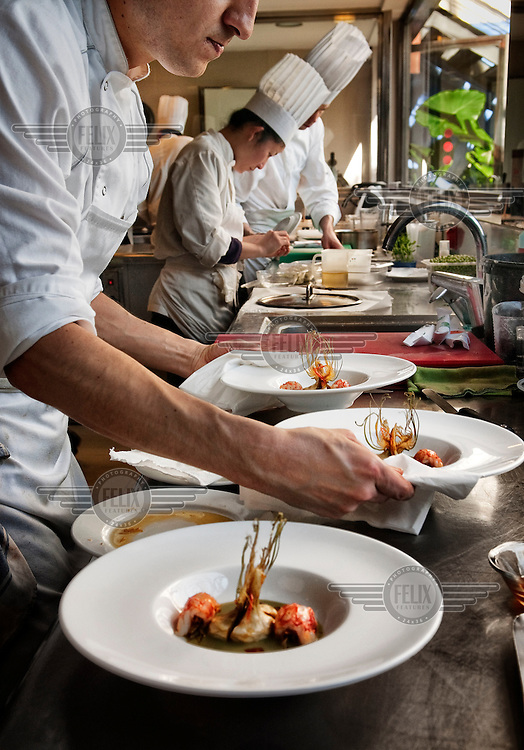 Chefs in Carmen Ruscalleda's restaurant Sant Pau prepare plates of food. People come from all over the world to train to be a chef at this restaurant.