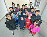 "Children pose for a photo in a church-sponsored ""child-friendly space"" in the village of Bakhtme, Iraq, which was flooded with displaced families when the Islamic State group took over nearby portions of the Nineveh Plains in 2014. The space is sponsored by the Christian Aid Program Nohadra - Iraq (CAPNI). It includes some children from the host community as well."