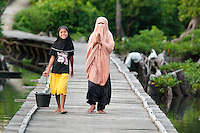 Pulau Batudaka, Togean Islands, Central Sulawesi, Indonesia. A muslim woman completely covered. The Bajau Sea Gypsies one roamed the seas as nomads. Nowadays they live an empoverished life of fishing and collecting trepang sea cucumbers from their stilted villages. In the 1990's they started cyanide and dynamite fishing causing major damage to the reefs and their future fish stocks. The Togean or Togian Islands are an archipelago of 56 islands and islets, in the Gulf of Tomini, off the coast of Central Sulawesi, in Indonesia. The dark green of the islands and the cristal clear water is a perfect setting and has attracted many travellers during the last years. Travellers endure the long journey in search of the mythical beach paradise. Photo by Frits Meyst/Adventure4ever.com