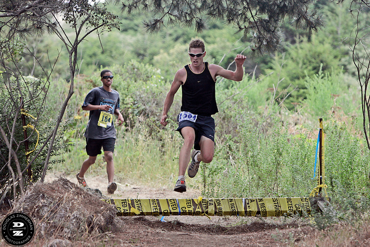 Jarred  Barrillfaux (1384) of Rohnert Park  jumps over a stile, as (164) Christopher Slatten  of Antioch runs behind and about to leap onto Highway 1 to race the final quarter-mile of  the 99th running of the Dipsea Race at Sintson Beach State Park in Stinson Beach, Calif. on Sunday June 14th, 2009.